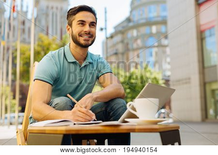 Commercial artist. Enthusiastic attractive ambitious guy enjoying warm weather and thinking about business concepts while working on them on a terrace