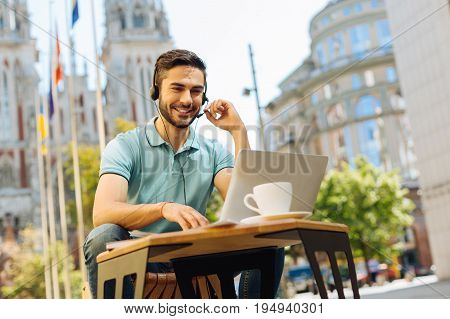 How can I help you. Savvy charismatic motivated man working distantly as a customer support representative and choosing his workplace with creativity