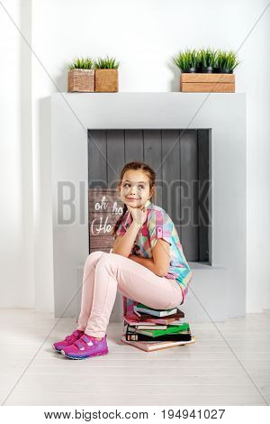 The child is sitting in the book in the room. The concept of education and childhood.