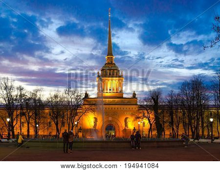 SAINT PETERSBURG RUSSIA - MAY 1 2017: Unknown people are resting near fountain at Main Admiralty building in evening St. Petersburg Russia