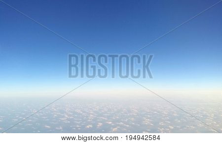 Cirrocumulus (small patched) cloud under blue sky separated by the horizon, topview from airplane window-natural background; concepts of freedom, peaceful, heaven, separate; top copyspace