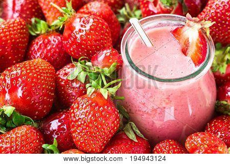 Beautiful appetizer red strawberry fruit smoothie. Yogurt cocktail. Close up. Natural detox. Liquid ice cream. Glass of strawberry milkshake with berries background, top view, selective focus.
