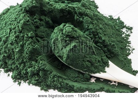 Spirulina Algae Powder close upon white background .Macro selective focus