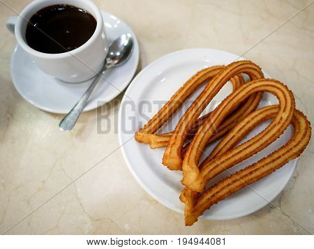 Churros or Spanish fried-dough pastry on white plate served with a cup of hot chocolate as dipping sauce.