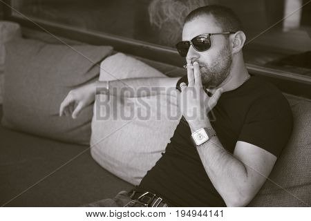 Vape man. Handsome young white guy smokes cigarette.Black and white photo.