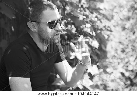 Vape man. Portrait of a handsome young white guy smokes cigarette.Black and white photo. Lifestyle.