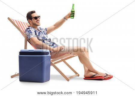 Tourist sitting in a deck chair next to a cooling box and toasting with a bottle of beer isolated on white background