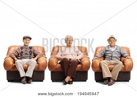 Two elderly men and an elderly woman sitting in leather armchairs and looking at the camera isolated on white background