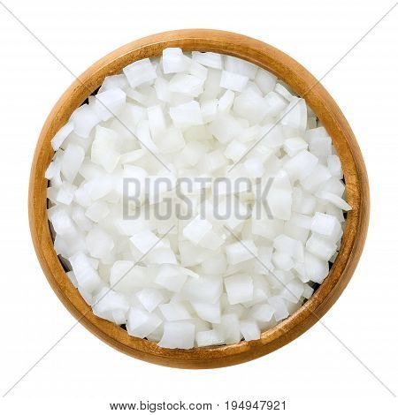 White onion cubes in wooden bowl. Chopped fresh, raw Allium cepa, also bulb or common onion. Vegetable, ingredient and staple food. Isolated macro food photo close up from above on white background.