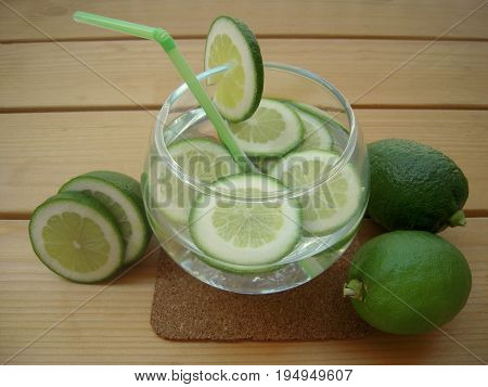 Lime water with slices of lime in a round cup with straw.