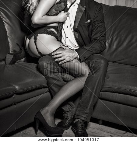 Rich man with young lover in underwear on sofa black and white