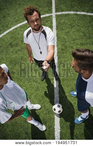 Overhead View Of Referee Throwing Coin Before Start Of Soccer Match On Pitch