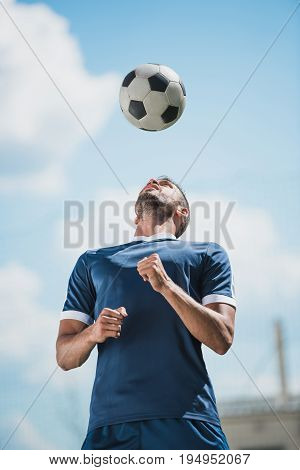Low Angle View Of Soccer Player Training With Ball On Soccer Pitch