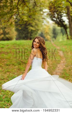 Stunning Bride Looks Over Her Shoulder While Whirling On The Green Hill