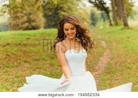 Wind Blows Bride's Hair While She Whirls Her Magnificent Dress On The Green Hill