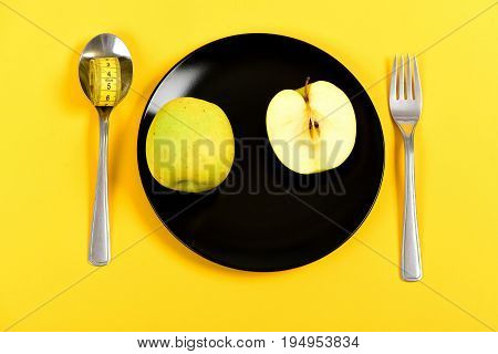 Plate Of Black Colour With Whole Apple Fruit And Half