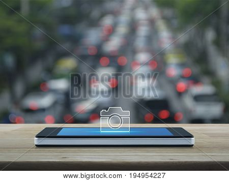 Camera icon on modern smart phone screen on wooden table over blur of rush hour with cars and road Camera online shop concept