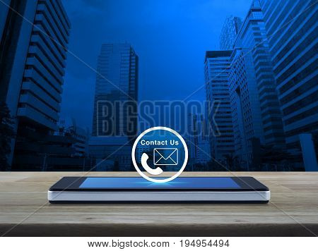 Telephone and mail icon button on modern smart phone screen on wooden table over modern office tower Contact us concept