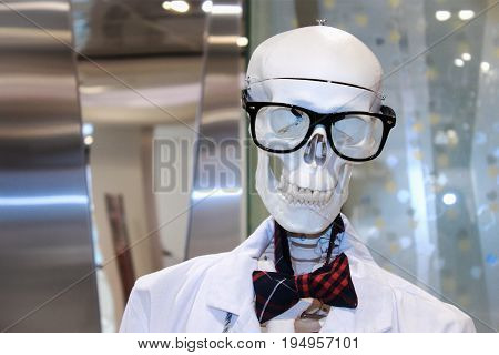 A skeleton wearing glasses and a bow tie in a shop window