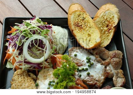 Mixed steaks recipe with vegetable salad and garlic toast.