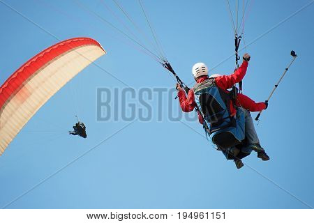 Two paraglider tandem fly against the blue sky,tandem paragliding guided by a pilot