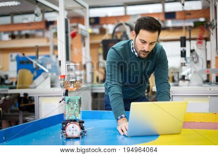 Young beutiful engineer testing his robot in workshop