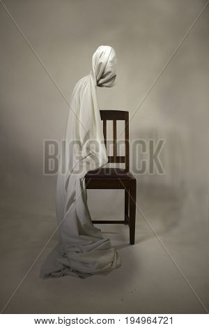 Ghostly figure with head wrapped in a bed sheet sitting on a dark brown seat.