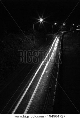 Black and white night time scene. Streams of light come from car tail lights which cross the frame.