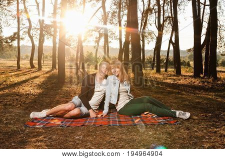 happiness of the couple sitting on a bedspread in the woods in the sunset