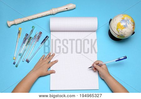 Open notebook with flute globe autumn leaves and hands of Caucasian primary school age girl. Education and school concept.