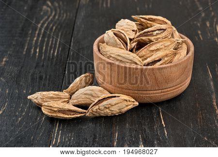 Wild uzbek inshell almonds in a bowl on wooden background