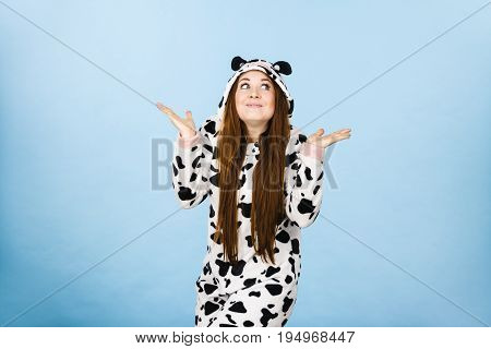 Teenage girl in funny nightclothes pajamas cartoon style making silly face shrugging woman in doubt doing shrug confused girl gesturing do not know sign studio shot on blue.