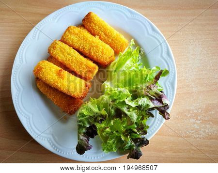 Top view of crispy fish fingers sticks and red green oak vegetables on a white plate (put on old wooden table); copy space on the right