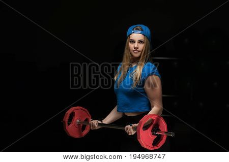 Portrait of blonde female exercising with barbell. Attractive fitness woman working out with weight. fitness and healthy lifestyle concept.