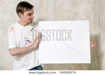 Painter's advertisement, new masterpiece, creativity and mockup concept. Craftsman pointing out on blank painting holding his hands