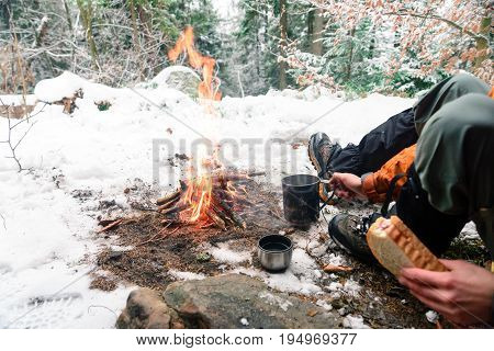 camping, travel, tourism, hike and people concept - man drinking hot tea near camp fire at camp in woods