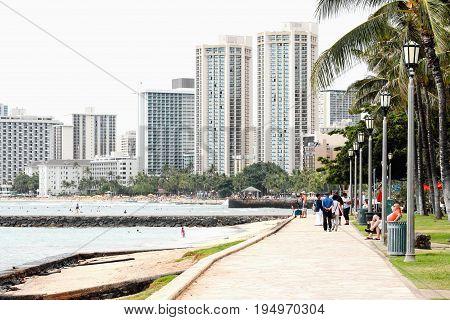 Honolulu Hawaii USA - May 28 2016:Walkway along Kuhio Beach looking toward Waikiki shops and hotels