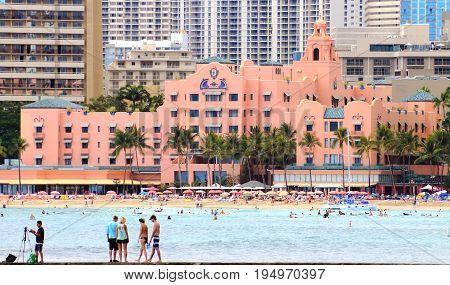 Honolulu Hawaii USA - May 28 2016:People enjoying Waikiki beach outside the Royal Hawaiian Center Waikiki Bay.