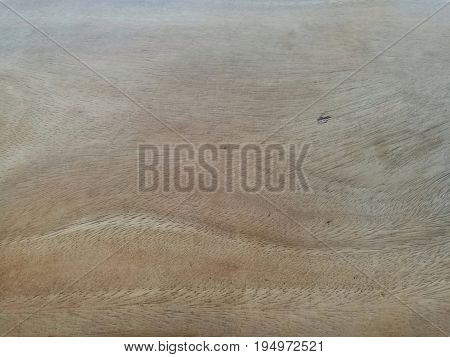 Close up of old wooden table surface with uneven color (pale on top) and many tiny scratched lines on pale area