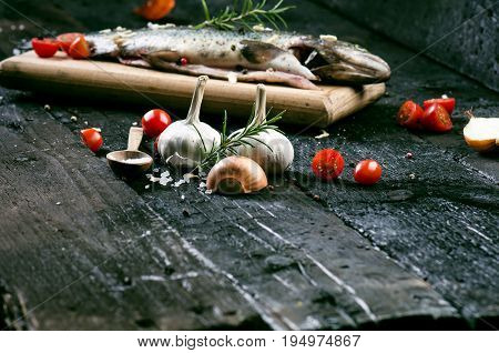 Fresh fish on a vintage black, burnt table. Wooden table. Fish with vegetables, salt, oil, herbs. Concept of cooking. Healthy and dieting food. Detail