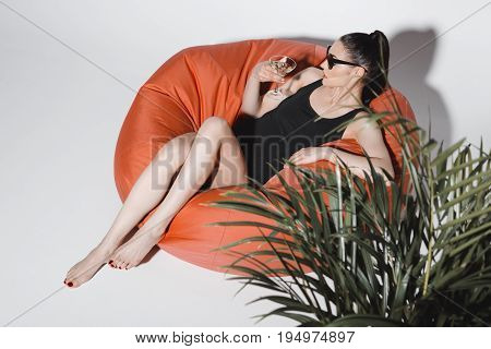 Gorgeous Young Woman In Sunglasses And Bodysuit Drinking Cocktail While Resting In Bean Bag Chair