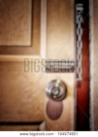 Blurred unclean door with door knob and unlocked security chain, vintage style with vignette. Concept of mysteriousness and insecurity.