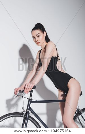 Pretty Young Brunette Woman In Fashionable Black Bodysuit Sitting On Bicycle And Looking At Camera