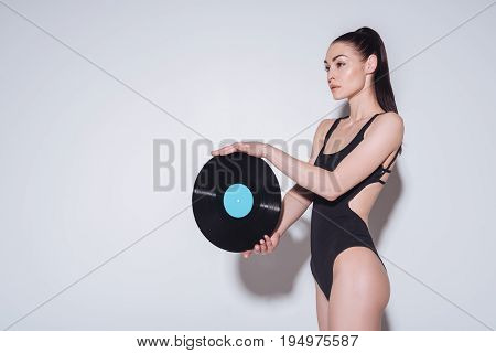 Beautiful Young Woman In Bodysuit Holding Vinyl Record On Grey