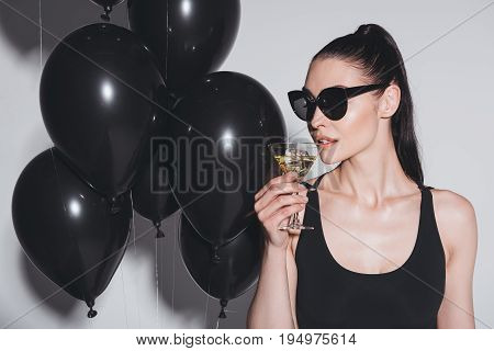 Gorgeous Young Woman In Sunglasses And Leotard Drinking Martini While Standing In Studio With Black