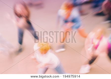 Abstract blurred background with group of unidentified people dancing on outdoor area. Top view. Concept of active healthy lifestyle, sport, leisure. For background , backdrop, substrate, colour trend