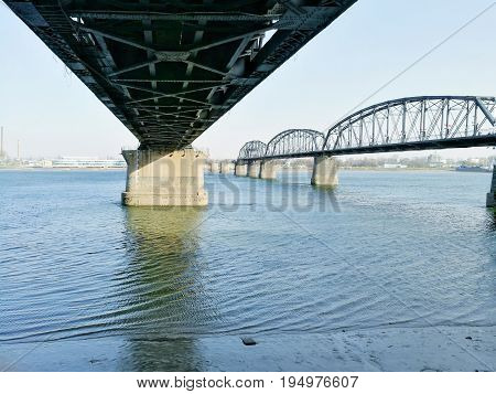 Beneath the bridge of China - North Korea  Friendship with Broken Bridge on the right; across Yalu river. Taken in April, 2017, from public area in Dandong, Liaoning, China, opposite to Sinuiju, DPRK.