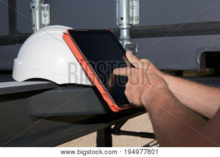 Businessman surfing of a digital tablet and reviewing a tack of containers