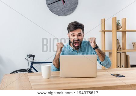Portrait Of Excited Businessman Looking At Laptop At Workplace In Office