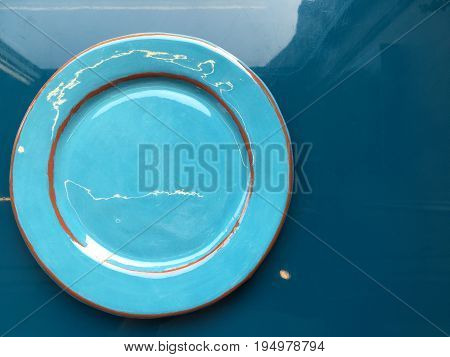 Light blue dish with orange rims. The plate stands on a blue glossy surface. Shooting from the top.